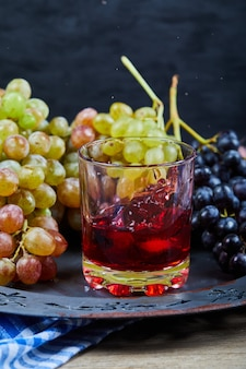 Bunch of grapes and a glass of juice on ceramic plate, close up.