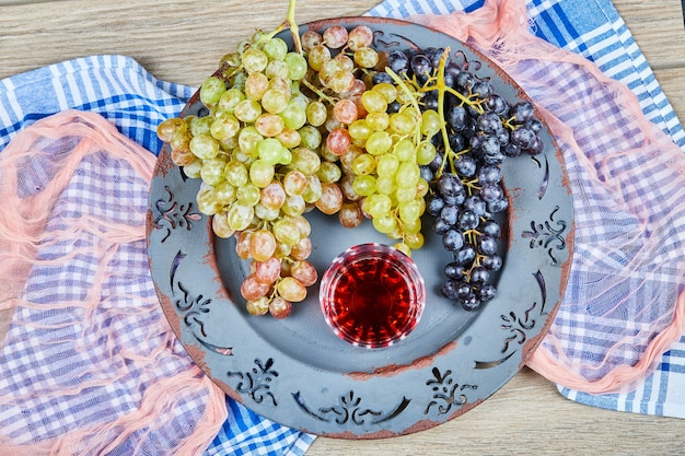 Bunch of grapes and a glass of juice on ceramic plate with tablecloths.