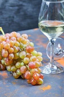 Bunch of grapes and a glass of wine on blue background. high quality photo
