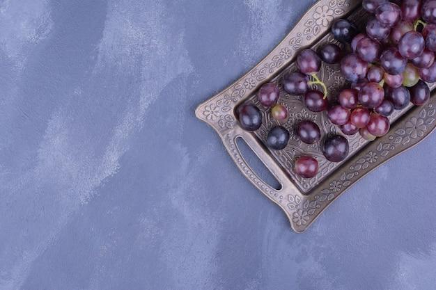 Un grappolo d'uva in un piatto metallico.