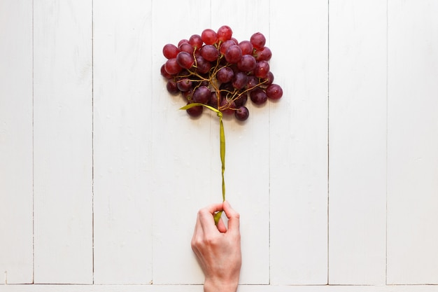 Bunch of grapes tied with a ribbon in a woman's hand