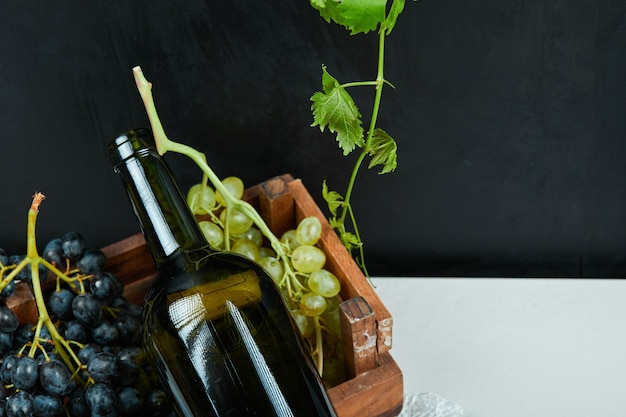 A bunch of grapes and a wine bottle on a white table. high quality photo