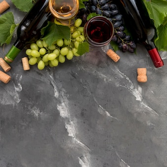 Bunch of grapes with bottle of wine on marble background