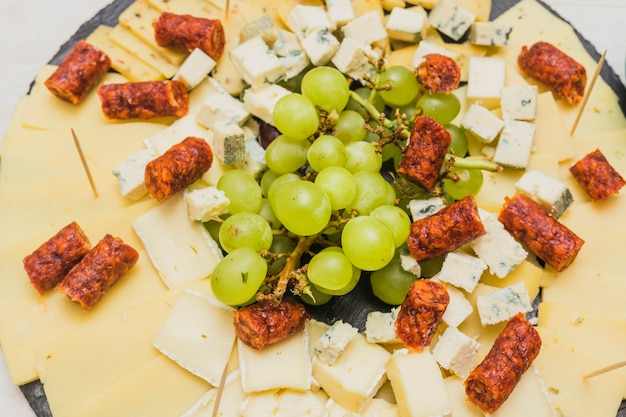 Bunch of grapes with cheese platter and smoked sausages on black slate board