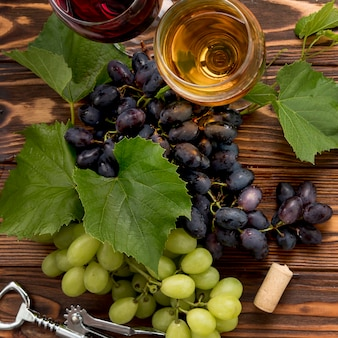 Bunch of grapes with corkscrew on wooden background