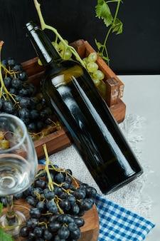 Un grappolo d'uva con un bicchiere di vino e una bottiglia sul tavolo bianco. foto di alta qualità