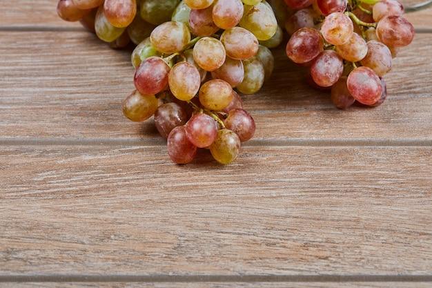 Un grappolo d'uva su fondo in legno. foto di alta qualità