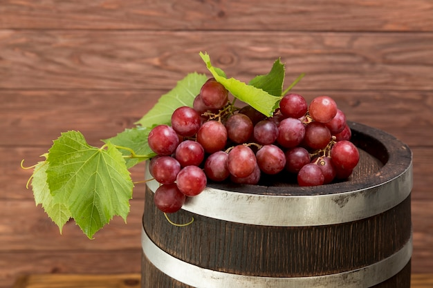 Bunch of grapes on wooden barrel
