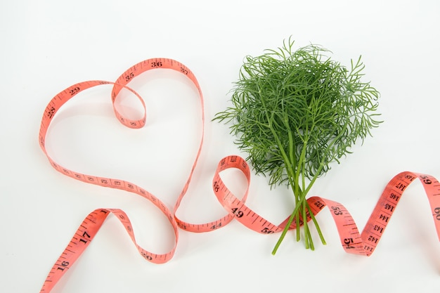 A bunch of green dill with a tape measure in the shape of a heart.