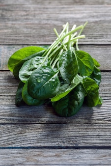 Bunch of green fresh spinach leaves on wooden table
