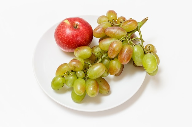 Bunch of green grapes and an apple on a plate with the white background. top view.