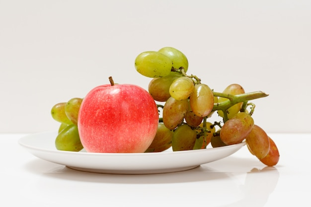Bunch of green grapes and an apple on a plate with the white background.
