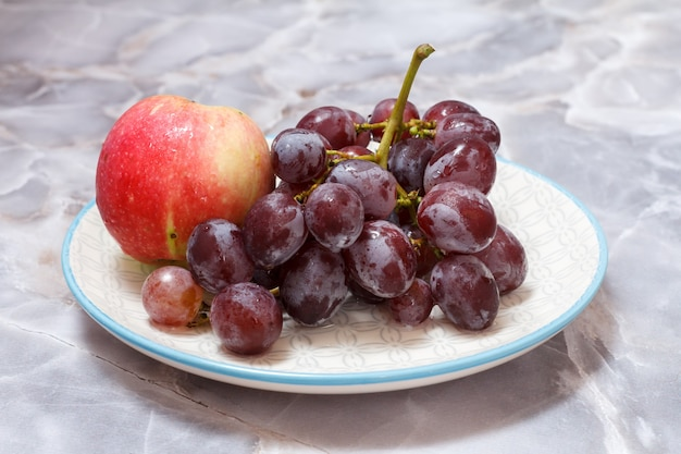 Bunch of green grapes and apple on white plate.