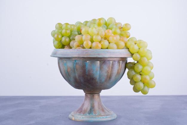 Un grappolo d'uva verde in un vaso metallico.