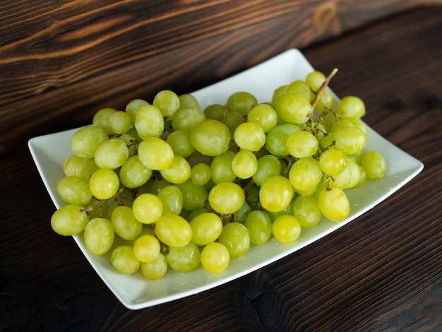 Гроздь зеленого винограда на деревянных