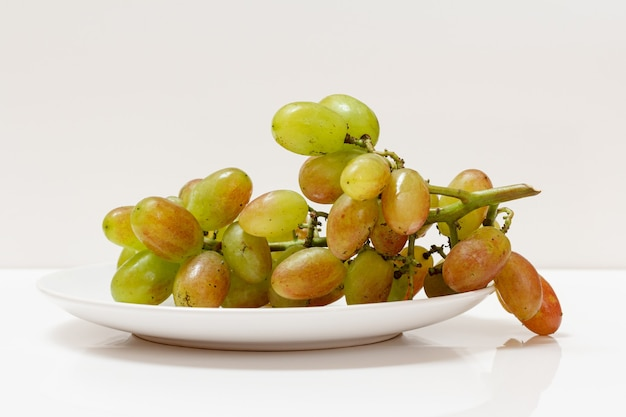Bunch of green grapes on a plate with the white background.