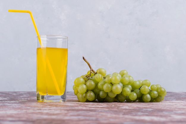Un grappolo d'uva verde con un bicchiere di succo sulla parete blu