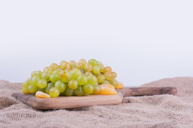 Un grappolo d'uva verde sul piatto di legno.