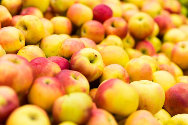 Bunch of green and red apples on boxes in supermarket and market