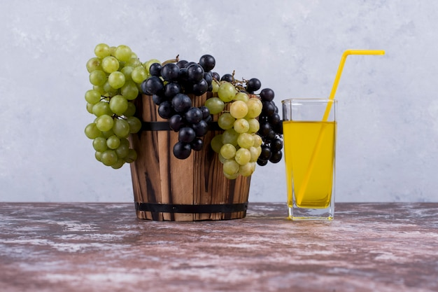 A bunch of green and red grapes in a bucket and a glass of juice
