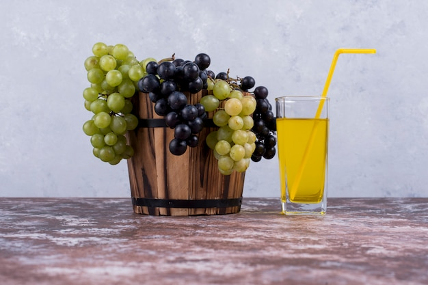 A bunch of green and red grapes in a bucket with a glass of juice