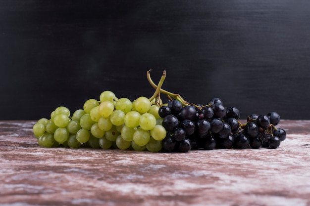 A bunch of green and red grapes on the table on black wall
