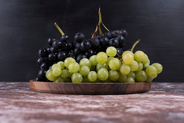 A bunch of green and red grapes in a wooden platter on black wall