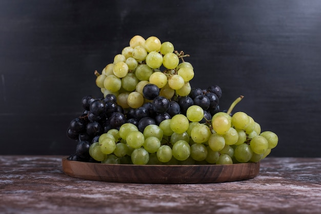 A bunch of green and red grapes in a wooden platter on black