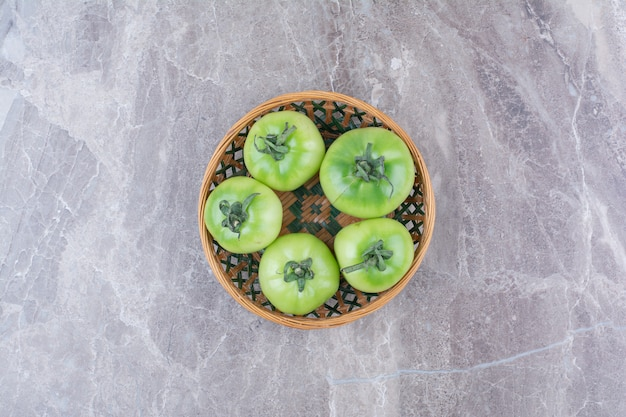 Bunch of green tomatoes in ceramic bowl.