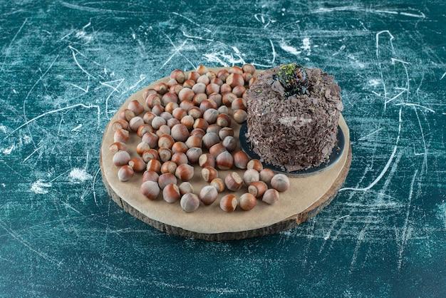 Mazzo di nocciole accanto a una piccola torta su una tavola sull'azzurro.