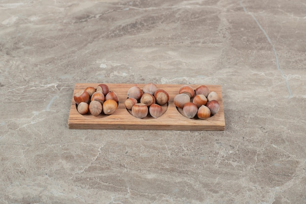 Bunch of hazelnuts in wooden plate on marble background. high quality photo