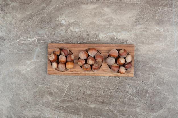 Mazzo di nocciole nel piatto di legno sulla parete di marmo.