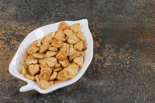 Mazzetto di cracker a forma di cuore su piatto a forma di foglia.