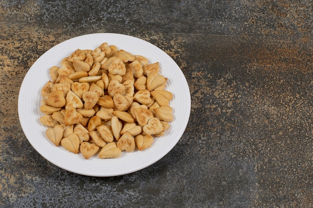 Mazzo di cracker a forma di cuore sul piatto bianco.