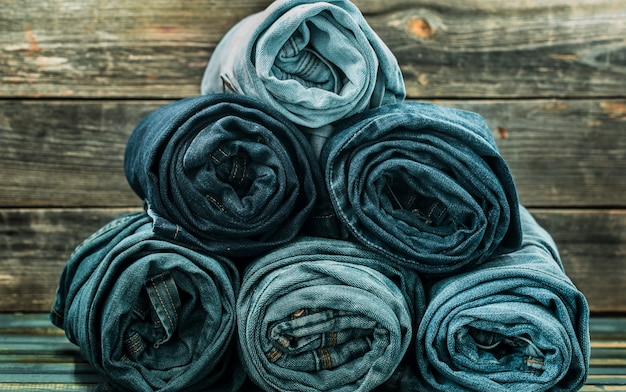Bunch of jeans twisted on a wooden wall, fashionable clothes