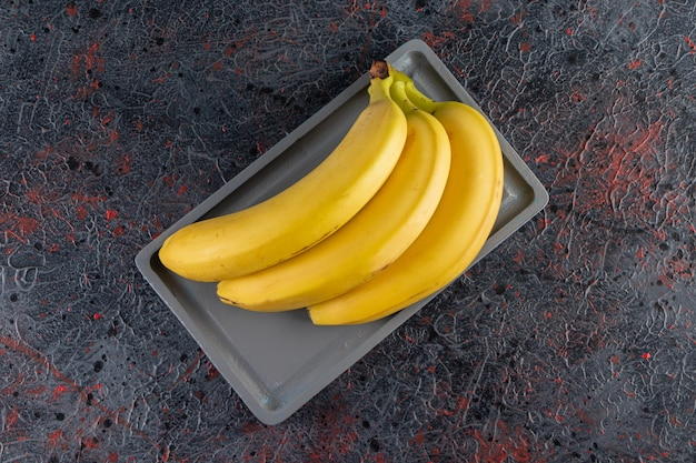 Mazzo di banana gialla succosa posta sul piatto scuro.