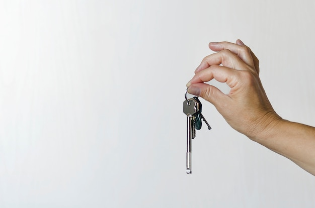 Bunch of keys in a female hand on a light background. new life. copy space