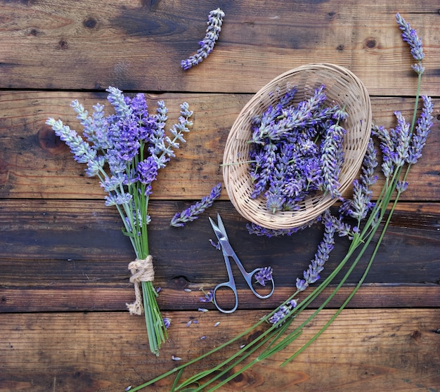 Bunch of lavender flowers next to a little basket full of petals  with scisors on wooden background