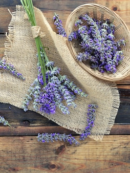 Bunch of lavender flowers on piece of fabric and basket on rustic wooden table