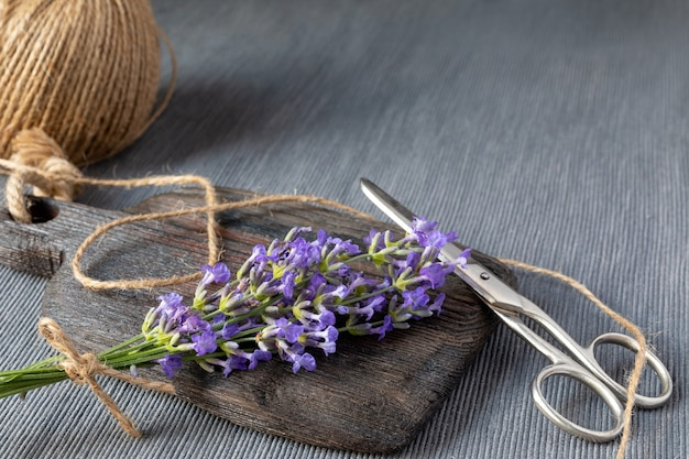 Bunch of lavender on wooden board, jute rope and scissors on gray background. concept of gardening, aromatherapy