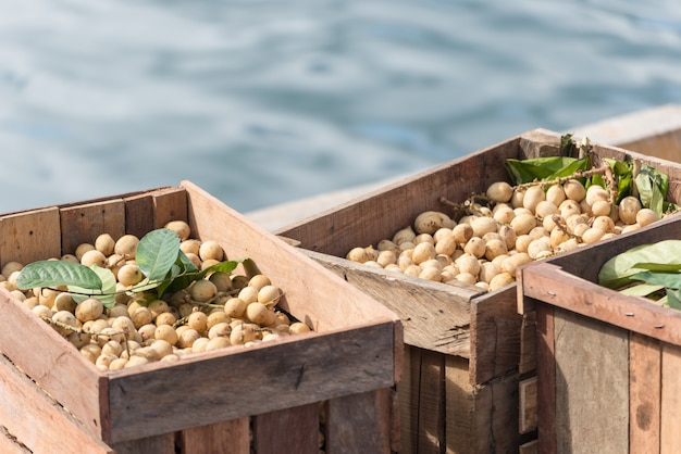 Bunch of longan tropical fruit stocked in wooden crates in indonesian market.