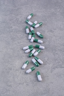 Bunch of medical capsules on marble table.