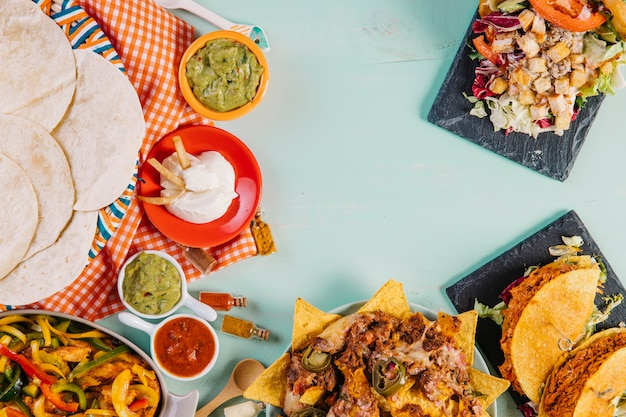 Bunch of mexican food near tablecloth