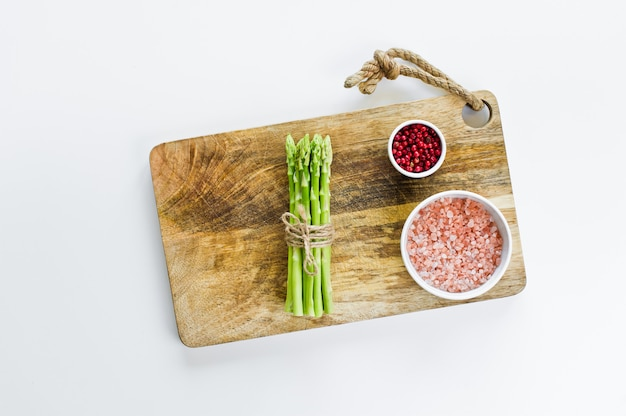 A bunch of mini asparagus on a wooden chopping board.