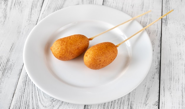 Bunch of mini corn dogs on white plate