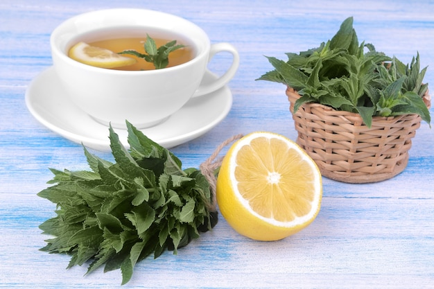 A bunch of mint with a lemon, a basket and a white cup of tea on a blue wooden background.