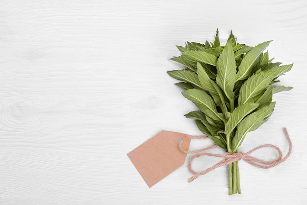 A bunch of mint with a sticker on a white wooden background, top view.