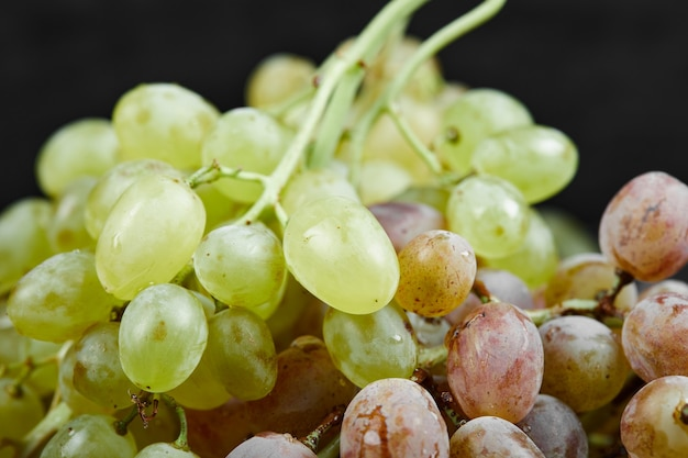 A bunch of mixed grapes on black surface
