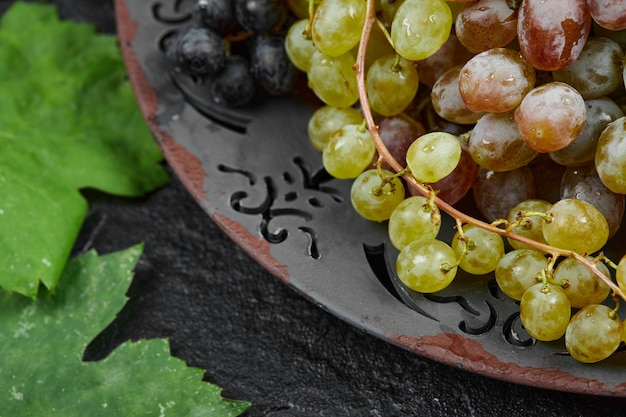 Un grappolo di uva mista su un piatto in ceramica. foto di alta qualità