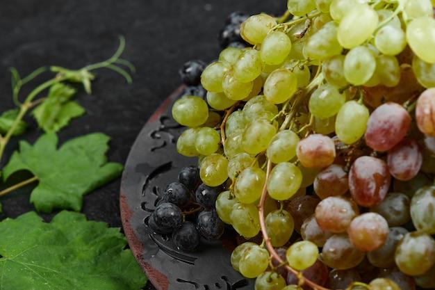 Un grappolo di uva mista su un piatto in ceramica con foglie. foto di alta qualità